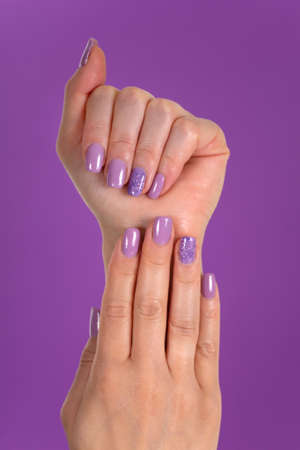 Beautiful woman hands with a lilac color nails polish gel isolated on purple background in the studio. Manicure and beauty concept. Close up, selective focus