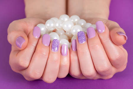 Beautiful female hand with a lilac color manicure holding pile of pearls isolated on purple background in the studio. Manicure and beauty concept. Close up, selective focus