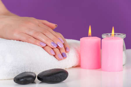 Beautiful female hands with a lilac color manicure on a white towel and pink decoration candle burning on the desk and purple background. Manicure and beauty concept. Close up, selective focus