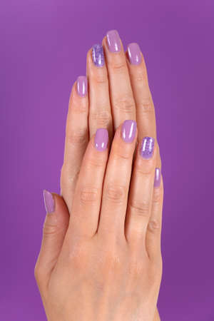 Beautiful female hands with a lilac color nails polish gel isolated on purple background in the studio. Manicure and beauty concept. Close up, selective focus