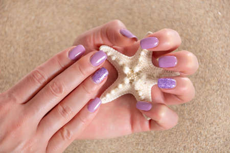Beautiful girl hands with a lilac color manicure holding starfish and sea sand in the background. Manicure and beauty concept. Close up, selective focus