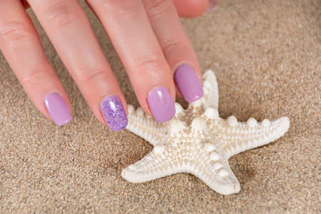 Beautiful girl hands with a lilac color manicure touch starfish and sea sand in the background. Manicure and beauty concept. Close up, selective focus 写真素材