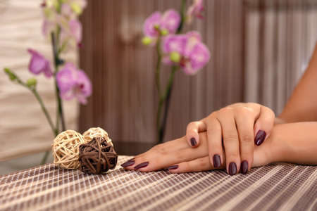 Woman hand with wine color nails polish on a desk and ball decoration on a desk in the beauty studio and blurred floral background. Manicure and beauty concept. Close up, selective focus