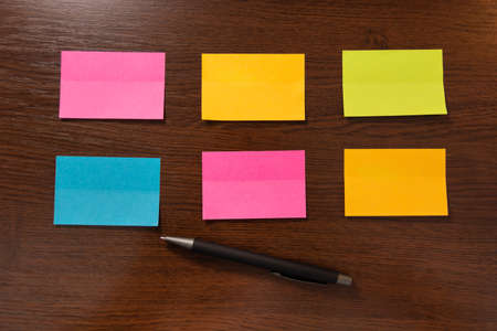 Six colorful sticky notes in two row and pen on brown wooden desk. Top view and space for text. Close up, selective focus 写真素材