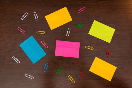 Colorful sticky notes and spilled paper clips on brown wooden desk. Top view and space for text. Close up, selective focus