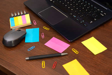 Colorful sticky notes and spilled paper clips, pen, computer mouse and laptop on brown wooden desk. Top view and space for text. Close up, selective focus