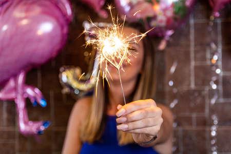 Cierge magique d'anniversaire brûlant dans la main d'une fille floue dans un restaurant décoré. Concept de célébration d'anniversaire. Gros plan, mise au point sélective