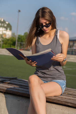 Attractive girl reading a magazine on the football grandstand and blurred football field in the background on a sunny summer day in the sunset. Close up, selective focus 版權商用圖片