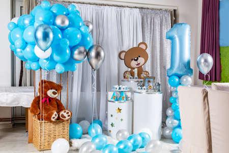 Leckeres süßes Geburtstagsbuffet mit Cupcakes, Baiser und anderen Desserts und Kinderspielzeugdekoration. Handgefertigter Kinderschreibtisch im Restaurant für die erste Geburtstagsfeier Standard-Bild