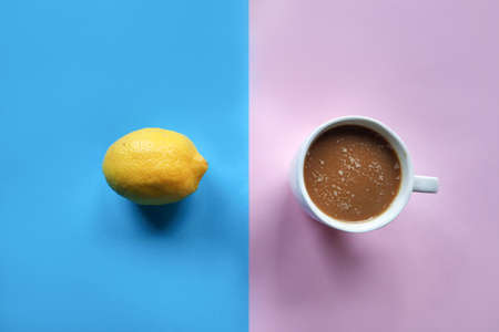 Lemon on blue and coffee cup on pink background. Home made food and drink concept. Close up, selective focus. Top view and shooting in a studio