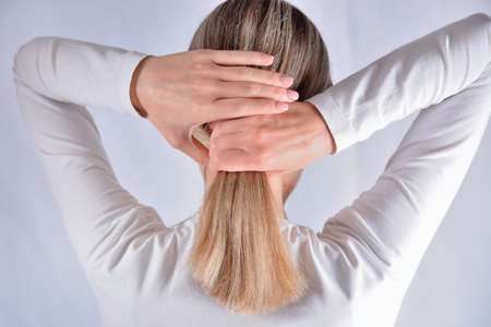 Young girl with blonde shaggy hair change hairstyles with hands. Attractive skinny girl isolated on studio white. Cares about healthy and clean hair. Close up, selective focus