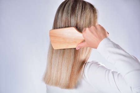 Young girl with comb brushing her blonde hair isolated in studio white background. Cares about healthy and clean hair. Beauty salon concept. Close up, selective focus Banque d'images