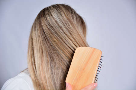 Young girl with wooden comb brushing her blonde hair isolated in studio white background. Cares about healthy and clean hair. Beauty salon concept. Close up, selective focus