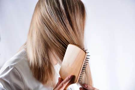 Young woman with wooden comb brushing her blonde hair isolated in studio white background. Cares about healthy and clean hair. Beauty salon concept. Close up, selective focus