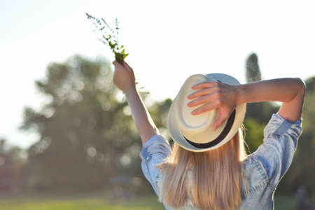 Woman holding in hand flowers raised in the air and holds a white hat on head. Blonde happy girl in nature on a sunny summer day. Relaxation in nature concept. Close up, selective focus