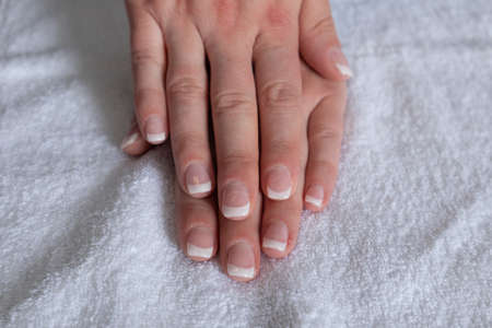 Female hands with french nails polish on a towel in beauty studio. Manicure and beauty concept, close up