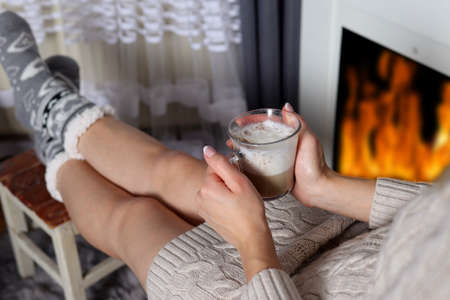 Female hand holding a cup of espresso coffee with milk foam on her legs and fireplace with flame in blurred background. Winter and drink concept