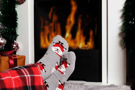 Girl warms her feet near the fireplace fire at home. Woman legs are covered with blanket and wear decorative Xmas socks. Winter and cold weather concept