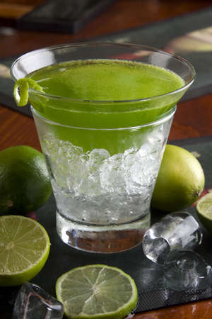icecube: Green cocktail with limes on a bar counter