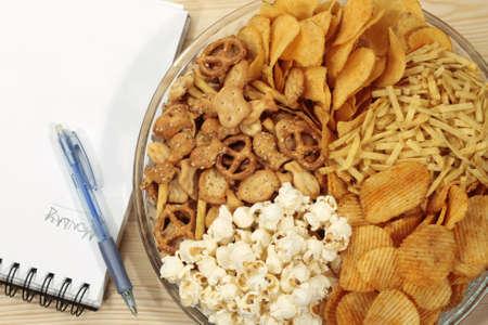 hoja en blanco: Distintos tipos de aperitivos cerca de la pluma y la hoja en blanco Foto de archivo