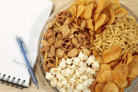 Various types of snacks near blank sheet and pen Stock Photo