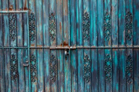 Rusted blue iron gateway with door photo