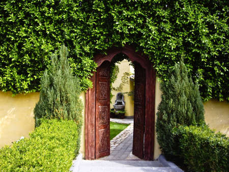spanish tile: Carved wooden doorway leads to secret garden