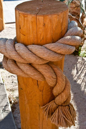 Nautical rope tied on wooden post Imagens