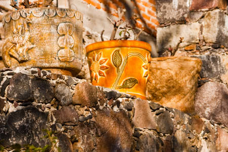 Mexican clay pots on stone wall Stock fotó