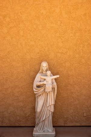 adobe wall: Statua della madre e del bambino sul muro di mattoni arancione Archivio Fotografico