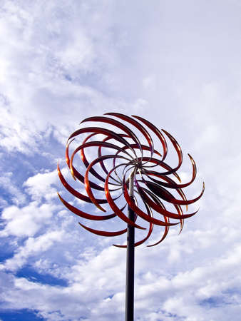 Wind moves the blades of red metal art photo