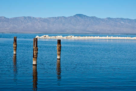 Posts reflect in water on a hazy summer day at Salton Sea California