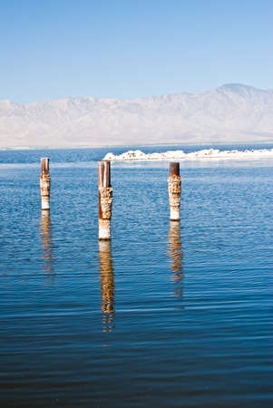 reflect: Posts reflect in water on a hazy summer day at Salton Sea California