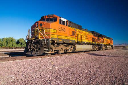 Needles, California, USA - February 5 2013: Distinctive orange and yellow Burlington Northern Santa Fe Locomotive freight train No. 5240 on the rail tracks.