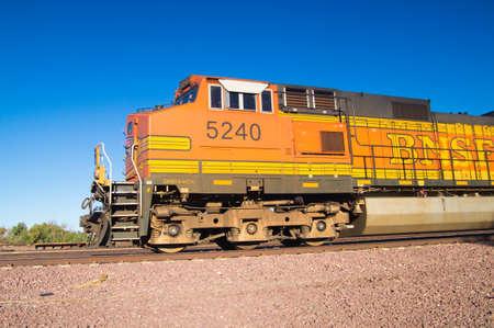 Needles, California, USA - February 5 2013: Distinctive orange and yellow Burlington Northern Santa Fe Locomotive freight train No. 5240 on the tracks outside town.