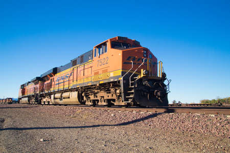 Needles, California, USA - February 5 2013: Distinctive orange and yellow Burlington Northern Santa Fe Locomotive freight train No. 7522 on the tracks. Stock fotó - 52639559