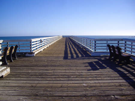 Long pier with two benches at coast