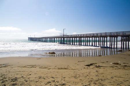 Pier on deserted beach California Coast