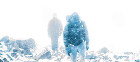 heavy risk: People hiking into blizzard during the day Stock Photo