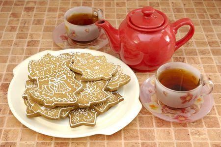 Two cups of tea, red kettle and gingerbread cookies on the plate Stock Photo - 5889630
