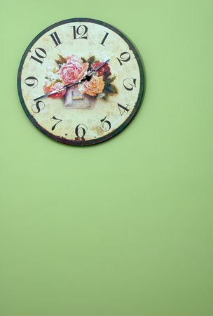 Vintage wall clock on the wall painted green photo