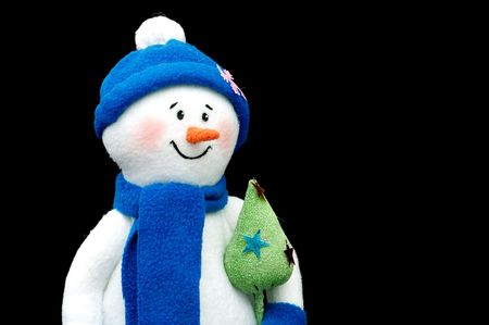 Handmade Snowman soft toy sewn from fabric over black background photo