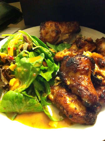 Honey Baked BBQ Chicken Wings with Arugula Salad drizzled in Spicey Peanut Vinegarette Sauce.