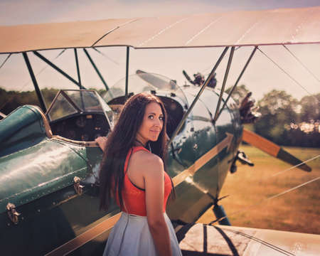 Woman waits by antique airplane.