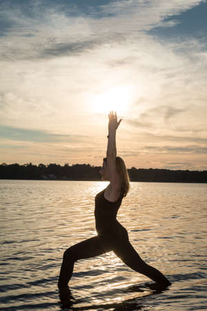 Yoga Teacher Doing Poses in the Lake Stock Photo