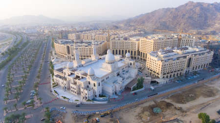 a white mosque in mecca surrounded by buildings and mountains