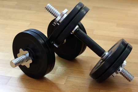Two dumbbells lying on a floor in a gym.
