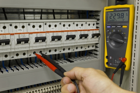 fusebox: Electrical engineer measuring voltage on a miniature circuit breaker.