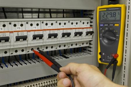 electricista: Ingeniero eléctrico midiendo el voltaje en un interruptor de circuito en miniatura.