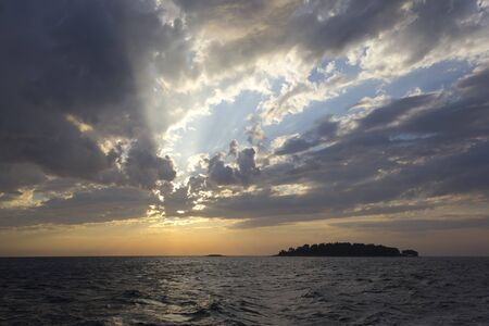 Sun rays through clouds at sunset over the sea. photo